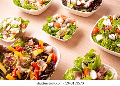 Mix of vegetable salads with dressing on wooden board