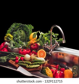 mix of vegetables and fruit in stainless steel sink, on black background