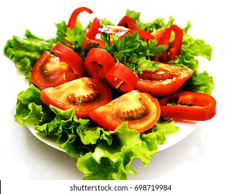 Mix of vegetables on a plate. Salad, tomatoes, Bulgarian pepper and parsley.