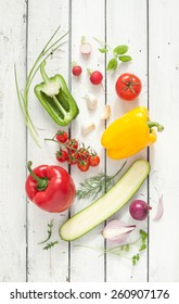 Mix of vegetables on white planked wood background - summer garden harvest. Red, yellow and green pepper, tomatoes, red onion, zucchini, radish, garlic and herbs from above.