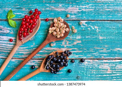Mix of white currant, red currant and black currant in different spoons on vintage wooden backglound