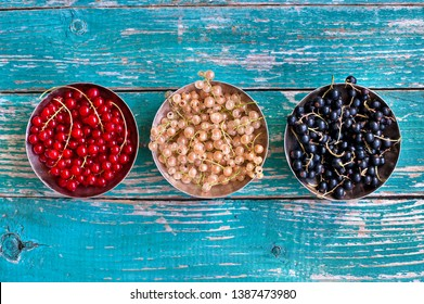 Mix of white currant, red currant and black currant  in a silver bowl on vintage wooden backglound
