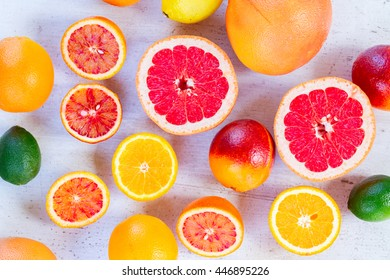 Mix of whole an cut citruses on white table, top view