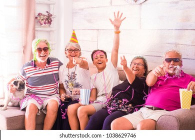 mixed ages with young and old people at home doing carnival party with masks. grandfather grandmother and newphew family with funny pug dog sit down on the sofa