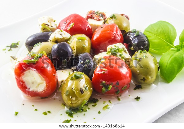 Mixed antipasti plate. Olives and peppers filed with cream cheese and feta cheese.