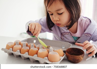 Mixed Asian girl planting seeds into eggshells, eco gardening,  montessori homeschooling education, reuse concept