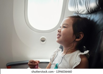 Mixed Asian girl watching movie inside airplane, family traveling abroad with children