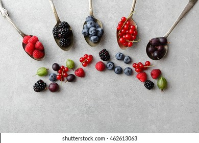 Mixed berries in old spoons on slate background