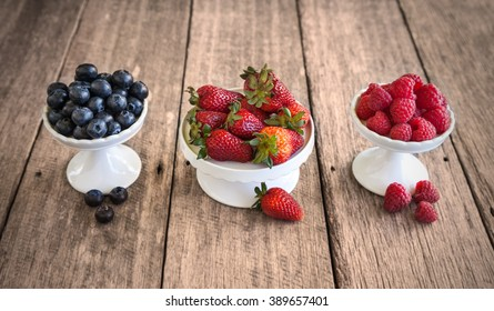 Mixed berries on white stands against wooden background