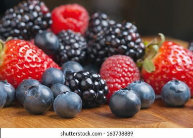 Mixed berries on a wooden background with selected focus.Strawberries, Raspberries Blackberries and Blueberries. Healthy Living and Nutritious Food concept.
