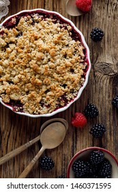 Mixed berry crumble in a baking dish on a wooden table, top view, close-up