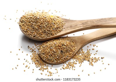 Mixed bird seeds, millet with wooden spoon pile isolated on white background