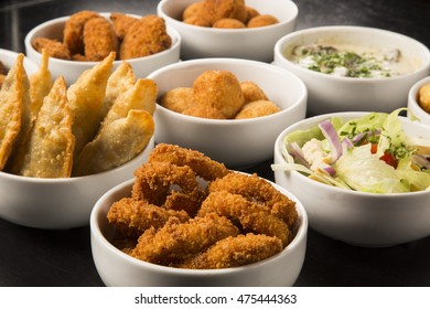 Mixed brazilian snacks, including pastries, fried chicken, salads, soups , fries , kibe .