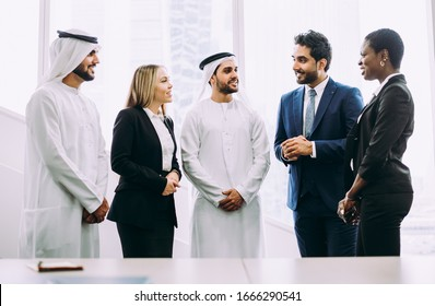 Mixed business team in Dubai. Business meeting with men wearing kandura and western people in the office