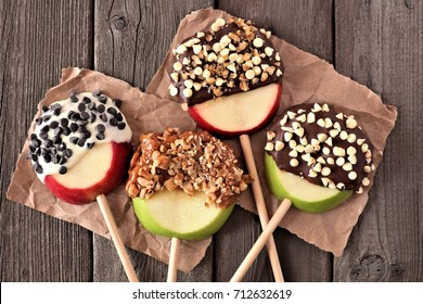 Mixed chocolate and caramel dipped apples rounds, above view on a rustic wood background