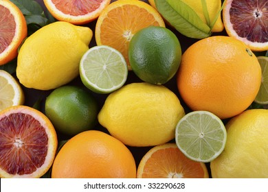 Mixed citrus fruit including navel and blood oranges, lemons and limes on dark wood table.