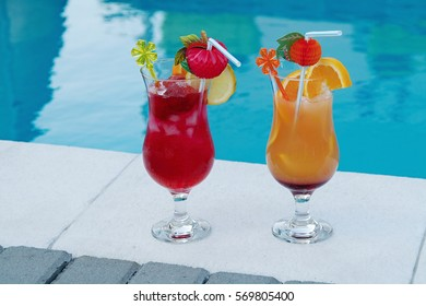Mixed colored drink in a tall glass with ice alcohol at the pool in the sea garden. Fruit cocktail with lime, lemon, strawberry, watermelon and orange