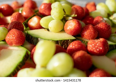 Mixed, colorful fruit salad served on a big glass plate.