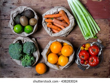 Mixed colorful fruits and vegetables  (orange, carrot, broccoli, celery, tomatoes, lemon, tomato cherry, blueberry and raspberry) in paper bag and basket creative draw on the wooden table