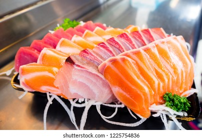 Mixed colorful raw fish Sashimi slice traditional Japanese food set includes Raw Salmon, Raw Tuna, Raw Yellow Tail (Hamachi) with sliced radish and parsley vegetable decoration (Object focus).