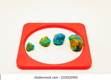 Mixed colors Modelling clay pieces surrounded by a red frame on a white background.