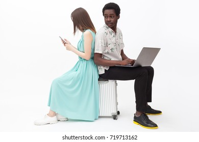 Mixed couple with a laptop and a phone sitting on a suitcase
