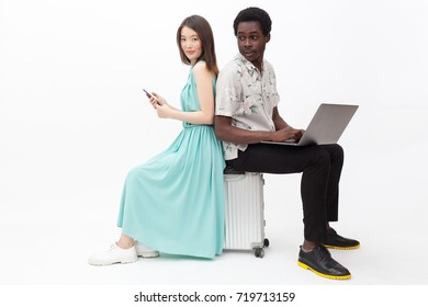 Mixed couple sitting on a suitcase