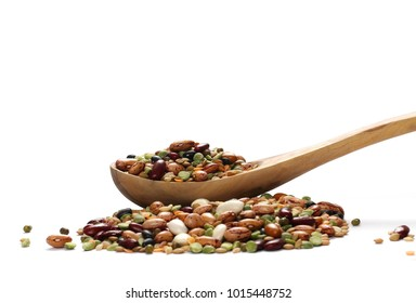Mixed dried legumes and cereals in wooden spoon isolated on white background