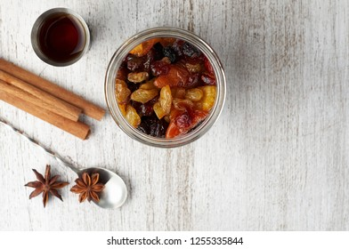 Mixed dry fruits and candied orange peel soaked with spices in rum for traditional Christmas Fruit Cake. Close up view on a vintage wooden background