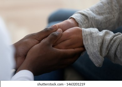 Mixed ethnicity family couple holding hands express support trust hope in marriage relationship, african black man friend husband give comfort compassion empathy to white woman wife, close up view