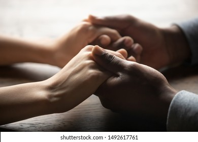 Mixed ethnicity family couple holding hands on table, black man friend husband support woman wife expressing love feelings, trust care honesty in interracial relationship concept, close up view