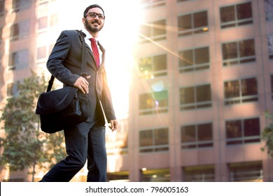 Mixed ethnicity male business man walking to work cheerful and enthusiastic near downtown buildings