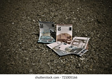 The mixed Euro banknotes lying on the sand ground. The concept of lost money.