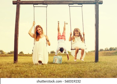 Mixed family having fun on the swing