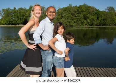 mixed family of Indian origin in front of the park lake during the summer holidays