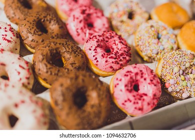 mixed flavours donuts in store display with colorful icinngs and sprinkles