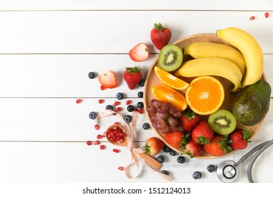 Mixed fresh fruit salad with strawberry with Stethoscope and blank notebook on wooden white background. Diet fruits concept and Flat lay, top view