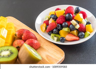 mixed fresh fruits (strawberry, raspberry, blueberry, kiwi, mango) on white plate