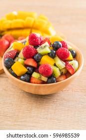 mixed fresh fruits (strawberry, raspberry, blueberry, kiwi, mango) on wood bowl