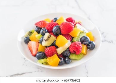 mixed fresh fruits (strawberry, raspberry, blueberry, kiwi, mango) on white plate