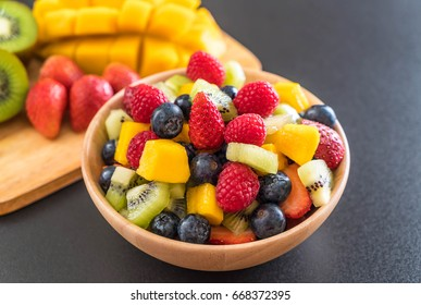 mixed fresh fruits (strawberry, raspberry, blueberry, kiwi, mango) on wood bowl