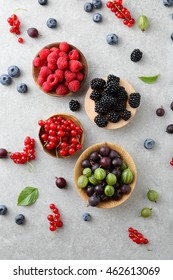 Mixed fresh ripe berries in bow on a slate background