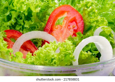Mixed fresh salad with curly coral lettuce, white onions and red tomatoes