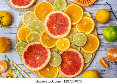 Mixed Fresh slices citrus fruit on a round wooden Board on a light background. Top view.