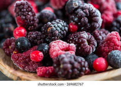 mixed frozen berries on wooden background, close view