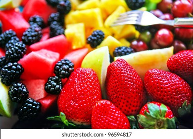 Mixed Fruit platter with fork strawberries blackberries pineapple and watermelon