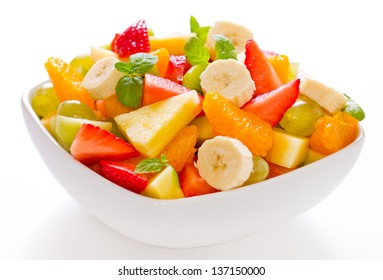Mixed fruit salad in the bowl on white background
