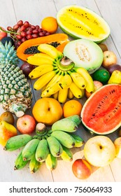 Mixed fruits with apple banana orange and other on wooden background - Healthy food style