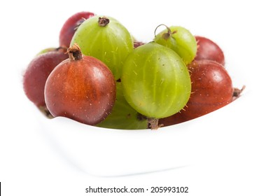 Mixed gooseberries in a white bowl isolated on white background.
