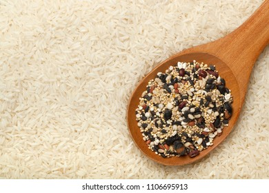 Mixed grains in a wooden spoon surrounded by rice